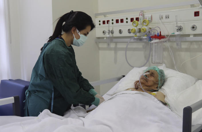 A nurse monitors Ayse Karatay at the City Hospital in Eskisehir, western Turkey, Saturday, Sept. 4, 2021. Karatay, a 116-year-old Turkish woman has survived COVID-19, her son said Saturday, making her one of the oldest patients to beat the disease. Ayse Karatay spent three weeks in intensive care and has now been moved to a normal ward, her son Ibrahim Karatay told the Demiroren news agency. (IHA via AP)