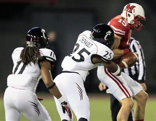 Cincinnati defensive back Arryn Chenault (25) knocks the ball loose from Miami (Ohio) receiver Andy Cruse (15) in the first half of an NCAA college football game on Saturday, Oct. 6, 2012, in Cincinnati. Cincinnati's Devan Drane (11) caught the loose ball before it hit the ground, for an interception. (AP Photo/Al Behrman)