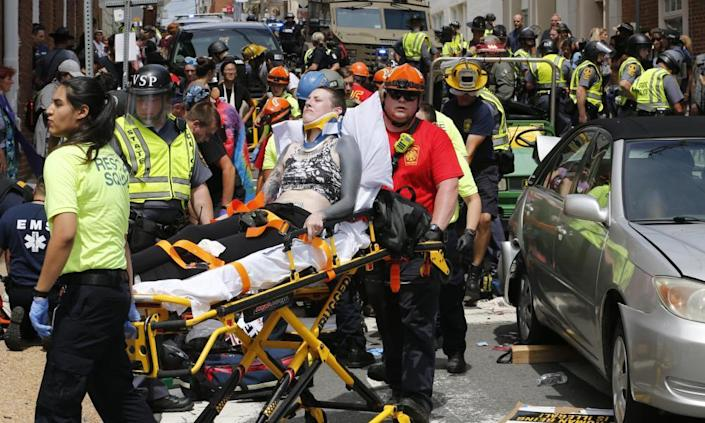 Rescue personnel help injured people after a car ran into a large group.