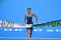 Flora Duffy of Team Bermuda celebrates as she crosses the finish line to win the gold medal during the women's individual triathlon competition at the 2020 Summer Olympics, Tuesday, July 27, 2021, in Tokyo, Japan. (AP Photo/David Goldman)