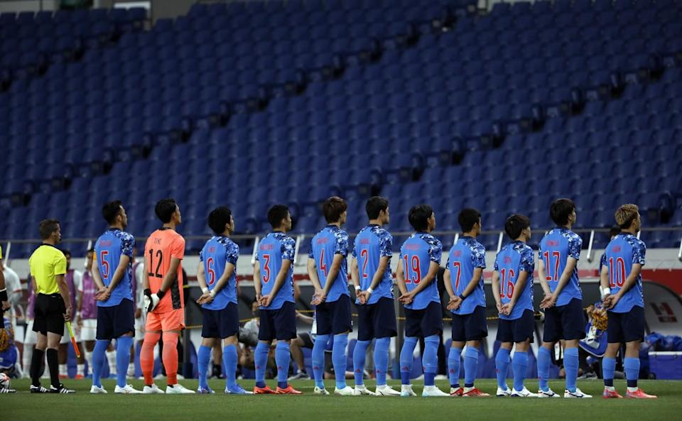 Soccer players stand in a line, hands clasped behind their backs, facing rows of empty stadium seats.