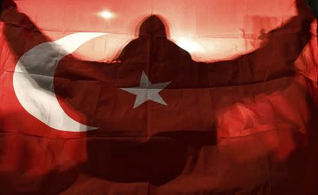 A demonstrator holds a Turkish flag outside the Turkish consulate in Rotterdam