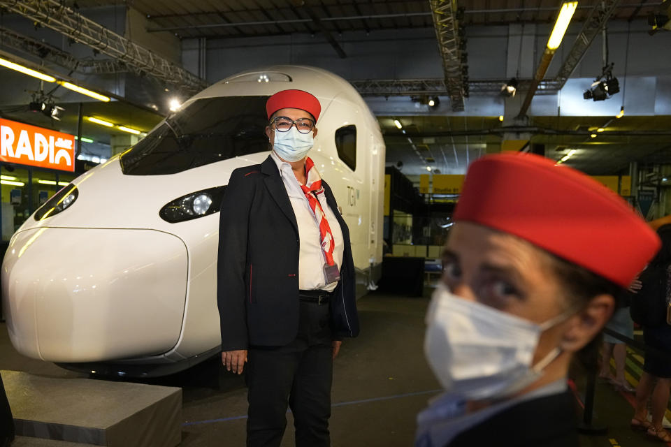 """Train employees pose by a life-size replica of the next high-speed train TGV is pictured at the Gare de Lyon station Friday, Sept. 17, 2021 in Paris. France unveils a super-fast, climate-friendly train of the future, the next generation of its high-speed TGV trains that have been emulated around the world. French President Emmanuel Macron and other government officials are holding a ceremony at the historic Gare de Lyon train station in Paris to mark 40 years since the unveiling of the first TGV, or """"train a grand vitesse."""" (AP Photo/Michel Euler, Pool)"""