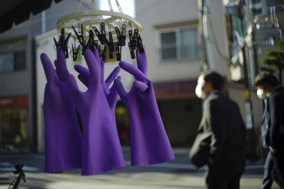 Rubber gloves hang to dry as people wearing protective masks to help curb the spread of the coronavirus walk past in Tokyo Thursday, Jan. 14, 2021. The Japanese capital confirmed more than 1500 new coronavirus cases on Thursday. (AP Photo/Eugene Hoshiko)