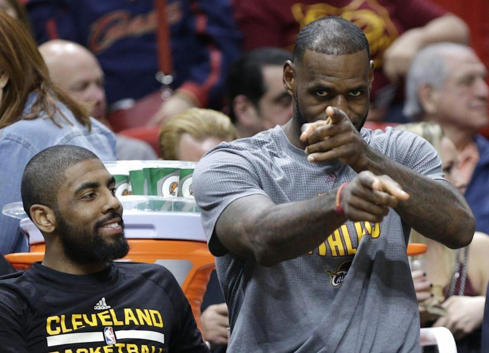 At least LeBron James gets paid to sit in a front-row seat. (AP)