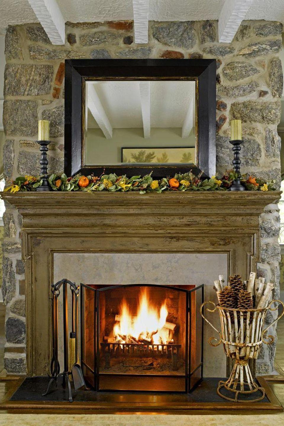 <p>When it comes to fall, it always pays to bring the outdoors in. Dressing up your mantel with dried leaves and mini pumpkins is an easy way to do it. </p>