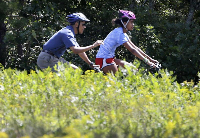 President Barack Obama and daughter Malia ride bicycles in Manuel F. Correllus State Forest in West Tisbury, Mass., Friday, Aug. 16, 2013. First Lady Michelle Obama and daughter Sasha, both not shown, passed by on the same path moments before. The first family are vacationing together on the island. (AP Photo/Steven Senne)