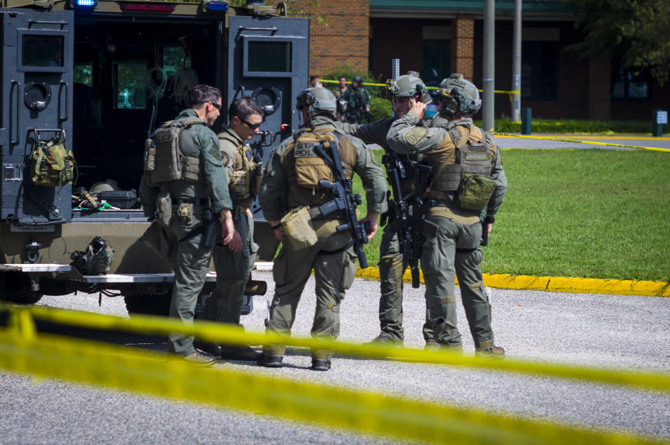 Members of the Virginia State Police SWAT Team gather behind a Bearcat tactical vehicle after clearing Heritage High School in Newport News, Va., Monday, Sept. 20, 2021, following a shooting at the school. (AP Photo/John C. Clark)