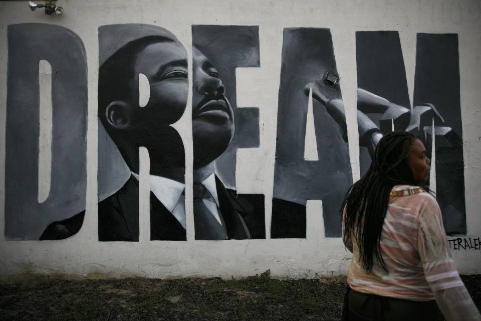 """Lorinda Lacy, 45, stands outside her party store painted with a mural depicting Martin Luther King Jr. in the Watts neighborhood of Los Angeles, Tuesday, June 30, 2020. Lacy moved out of Watts 20 years ago because she didn't want her daughters to grow up with the trauma she experienced as a girl. She said she eventually became """"immune"""" to the violence after stepping over bodies on the way to school and finding out who had been killed the night before or who had their house shot up. (AP Photo/Jae C. Hong)"""