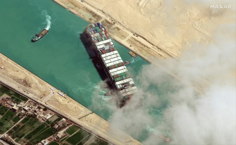 (FILES) In this file satellite imagery released by Maxar Technologies on March 29, 2021 the MV Ever Given container ship being pushed by tugboats in the Suez Canal. Egypt has signed a non-disclosure agreement with the Japanese owner of a megaship that blocked the Suez Canal in March as it finalises a compensation agreement, the canal authority chief said on June 24, 2021. Egypt has been seeking hundreds of millions of dollars in compensation from Japanese firm Shoei Kisen Kaisha for lost canal revenues and the costs of salvaging the ship and repairing the damage to the canal.