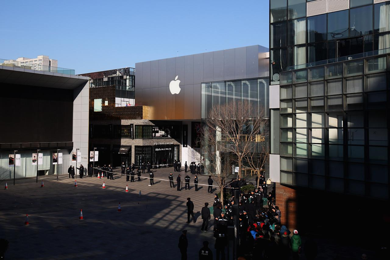 BEIJING, CHINA - JANUARY 13:  Police officers seal off the area near Apple's Beijing flagship store on January 13, 2012 in Beijing, China. Chinese angry crowd shouted and threw eggs outside Apple's Beijing flagship after it failed to open on schedule Friday to sell iPhone 4S.  (Photo by Feng Li/Getty Images)