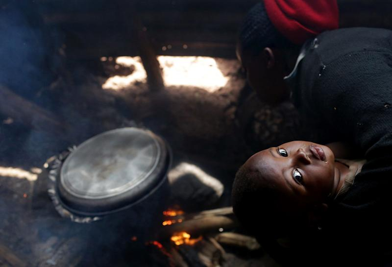 Marie Claire Nyirahabumufasha, 31-year-old mother to Nayituriki Bienvenu, holds her one-year-old as she cooks potatoes in a small hut near her restaurant in Kigali village in Rwanda, on November 12, 2017. Marie Claire hires others to bring her wood for cooking, and says her eyes and throat often hurt from doing so over smoke. She added she would definitely prefer using biogas over firewood if she had the option. (Photograph by Yana Paskova)