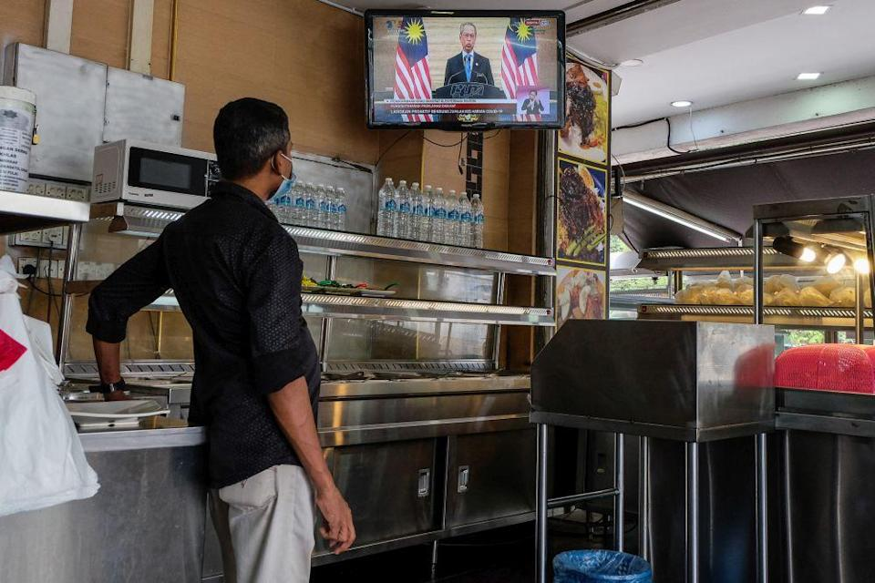 A man watches a live telecast of Prime Minister Tan Sri Muhyiddin Yassin's speech at a restaurant in Shah Alam January 12, 2020. — Picture by Yusof Mat Isa
