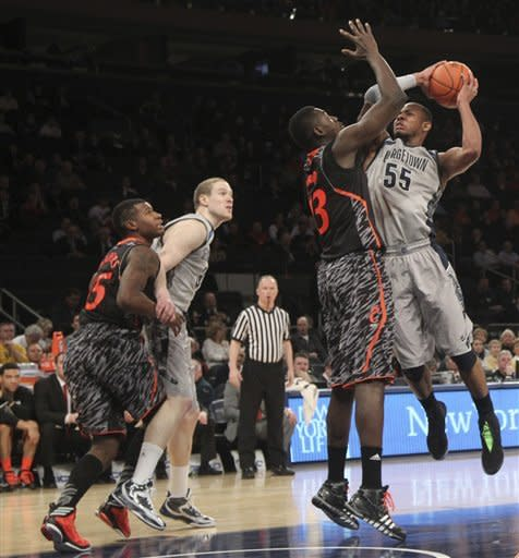 Georgetown's Jabril Trawick (55) goes up against Cincinnati's Cheikh Mbodj (13) during the first half of an NCAA college basketball game at the Big East Conference tournament, Thursday, March 14, 2013 in New York. (AP Photo/Mary Altaffer)