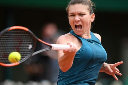 Rollercoaster victory: Simona Halep returns the ball to  Alison Riske on Wednesday