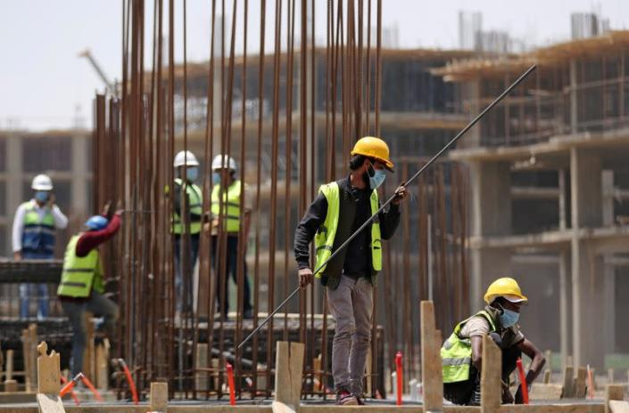 Workers wearing protective face masks stand on a building under construction in the New Administrative Capital (NAC), east of Cairo