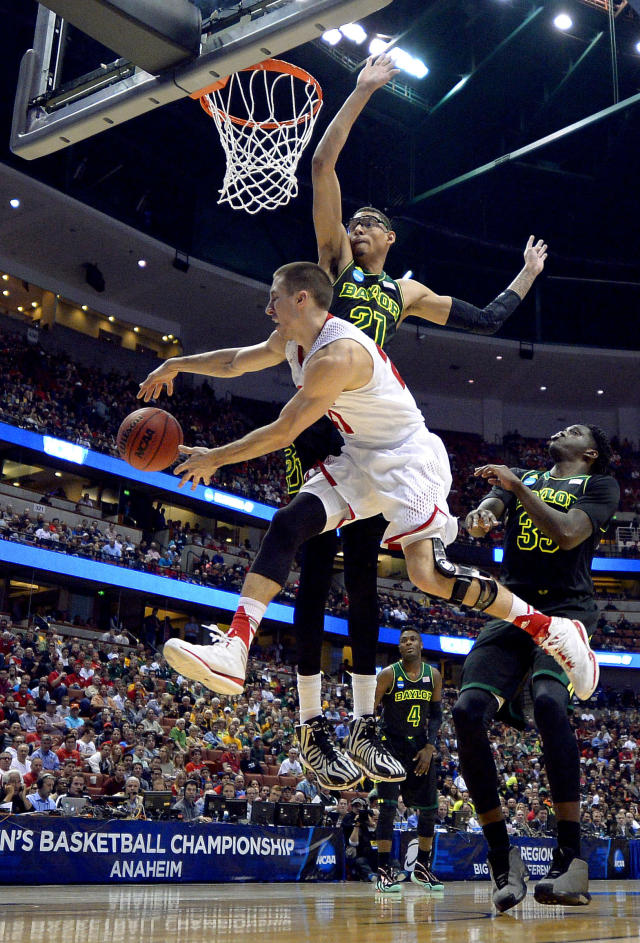Wisconsin guard Josh Gasser passes round Baylor center Isaiah Austin (21) during the second half of an NCAA men's college basketball tournament regional semifinal, Thursday, March 27, 2014, in Anaheim, Calif. (AP Photo/Mark J. Terrill)
