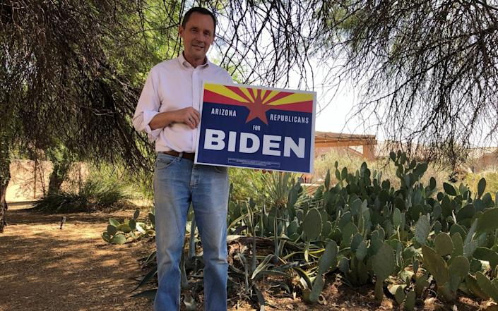 """A tall, white, older man with close-cropped black hair, jeans and wearing a white buttoned shirt with its sleeves rolled up, holds a sign that reads """"ARIZONA REPUBLICANS FOR BIDEN"""". He is standing amid cacti in a bright back yard, with the low shape of his house just visible through bushes and trees behind him - Laurence Dodds/Telegraph"""