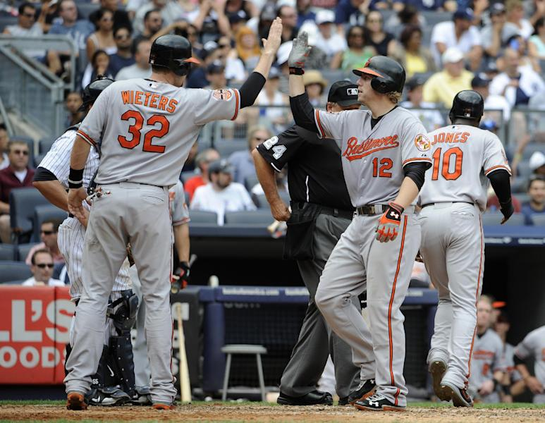Baltimore Orioles' Matt Wieters (32) greets teammate Mark Reynolds at home plate after Reynolds hit a three-run home run off New York Yankees starting pitcher Phil Hughes that also scored Wieters and Adam Jones (10) in the sixth inning of a baseball game on Sunday, Sept. 2, 2012, at Yankee Stadium in New York. Reynolds hit a solo home run in the fifth inning. (AP Photo/Kathy Kmonicek)
