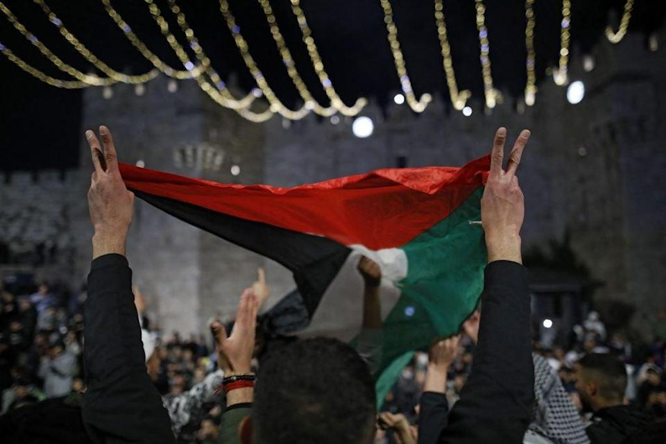 <p>Palestinian protesters wave the national flag outside the Damascus Gate in Jerusalem's Old City on 26 April, 2021</p> (Ahmad GHARABLI (AFP via Getty Images))