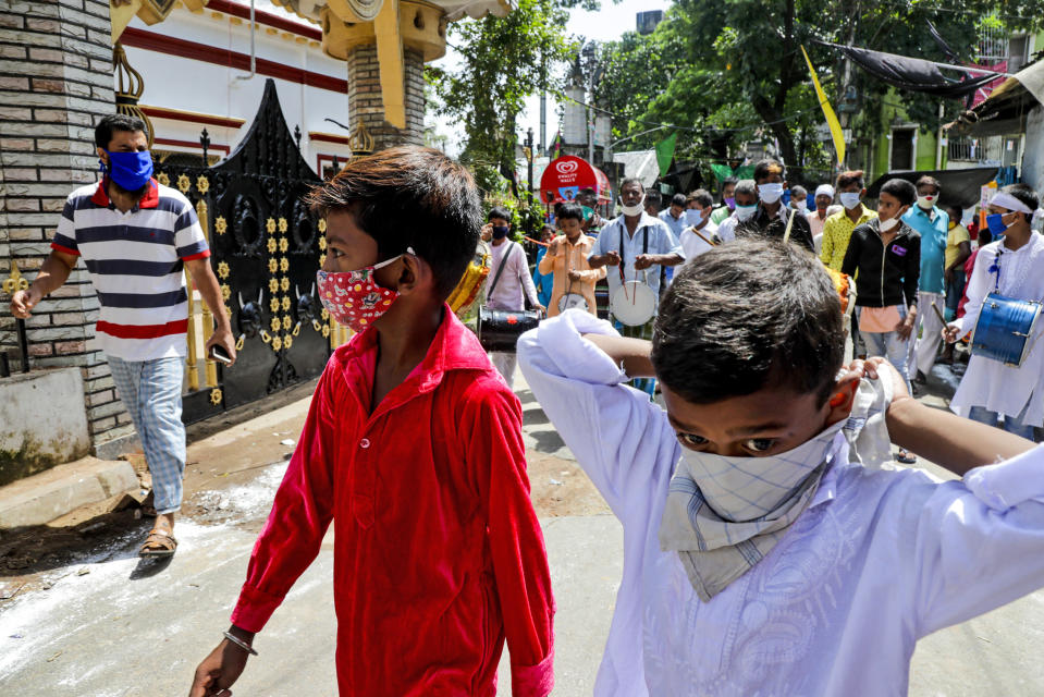 Muslims wearing face masks beat drums as they take part in a Muharram procession in Kolkata, India, Sunday, Aug. 30, 2020. India has the third-highest coronavirus caseload after the United States and Brazil, and the fourth-highest death toll in the world. (AP Photo/Bikas Das)