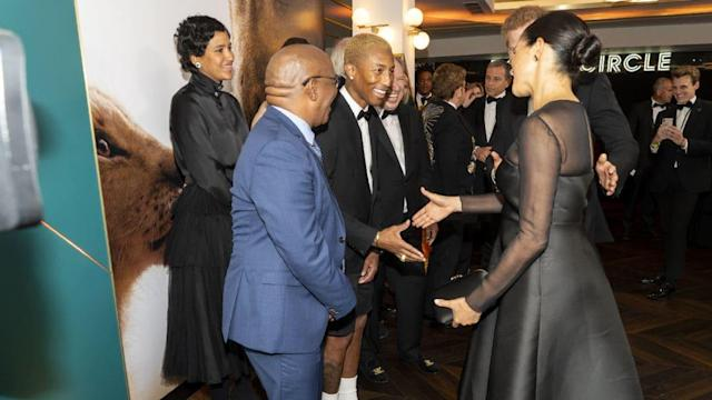 """WPA PoolTraditionally the royals walk a fine balance at public events and when meeting celebrities and members of the public.They try to take an interest and perhaps share a joke but, they tend to stop short of disclosing personal details.Now footage has surfaced of Meghan Markle appearing to break that cardinal rule by perhaps oversharing in a candid exchange with Pharrell Williams in which she appeared to suggest she is struggling to cope with royal life.The encounter happened at the premiere for the new Disney remake of The Lion King on Sunday (stealing the Wimbledon thunder from Kate Middleton) and began with Harry commenting on Pharrell's outfit, a combination of a tux and shorts.Meghan Hugs Beyoncé, and Totally Steals Kate Middleton's Wimbledon ThunderPharrell then said to Harry and Meghan; """"I'm so happy for your union. Love is amazing. It's wonderful… Don't ever take that for granted, but what it means in today's climate, I just wanted to tell you it's so significant for so many of us. Seriously.""""Meghan replied: """"That's so kind of you to say."""" Pharrell wasn't done however and said: """"I mean this. It's significant. We cheer you guys on."""" Meghan reached out and touched him on the arm, saying: """"Oh thank you. They don't make it easy.""""Pharrell then appeared to say, after a whispered exchange, """"So you understand the significance. It's beautiful.""""With video of the exchange now going viral on Twitter, an online debate is raging about exactly what Meghan is referring to. U.K. papers, never wanting to pass up any opportunity to do so, have used the exchange as an excuse to attack Meghan, with the Mirror, for example, saying she was """"moaning about life in the public eye."""" In fact, Meghan said or implied nothing about being """"in the public eye,"""" nor did Pharrell, as the clip clearly shows.While her unguarded comment clearly shows she has struggled to adapt to her new role, it seems likely that Pharrell was praising, in her marriage to Harry, the arrival of the first biraci"""