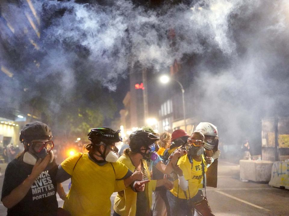 Members of Moms United for Black Lives Matter brace themselves against tear gas fired by federal officers in Portland, Oregon: Getty Images