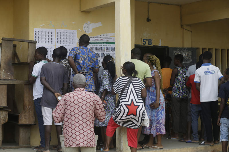Voters search for their names before casting their votes in the presidential election in Lome, Togo, Saturday, Feb. 22, 2020. The West African nation of Togo is voting Saturday in a presidential election that is likely to see the incumbent re-elected for a fourth term despite years of calls by the opposition for new leadership. (AP Photo/Sunday Alamba)