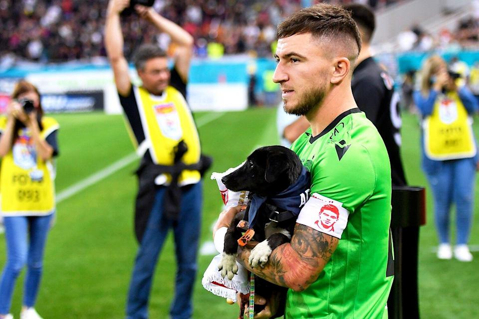 Deian Sorescu holds a dog before enter the pitch in action during the Romania Liga 1 game between FCSB and Dinamo Bucharest, played on Arena Nationala, in Bucharest, on Sunday 12 September 2021.