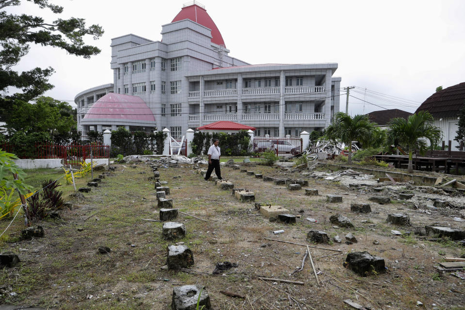 In this Wednesday, April 10, 2019, photo, a security guard walks amongst the ruins of the Tonga's historic Parliament House destroyed last year in Cyclone Gita in Nuku'alofa, Tonga. China is pouring billions of dollars in aid and low-interest loans into the South Pacific, and even in the far-flung kingdom of Tonga there are signs that a battle for power and influence among much larger nations is heating up and could exact a toll. (AP Photo/Mark Baker)