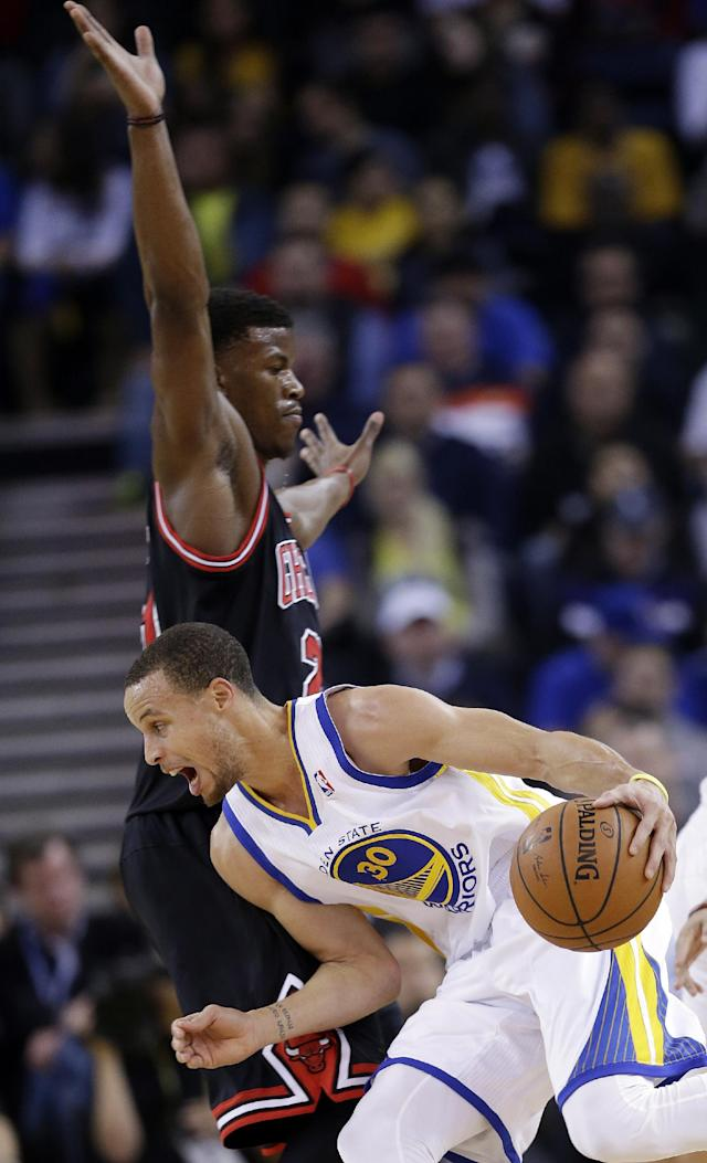 Golden State Warriors' Stephen Curry (30) dribbles around Chicago Bulls' Jimmy Butler during the first half of an NBA basketball game, Thursday, Feb. 6, 2014, in Oakland, Calif. (AP Photo/Marcio Jose Sanchez)