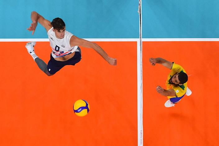 <p>USA's Torey Defalco spikes the ball in the men's preliminary round volleyball match against Brazil.</p>