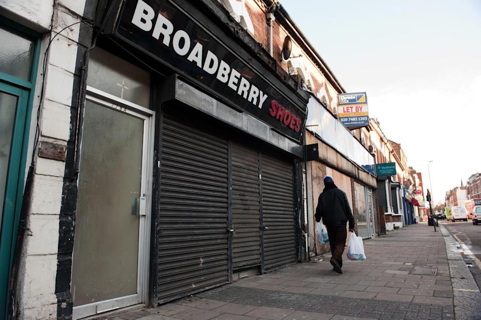 A shopper walks past a shuttered closed-down shop on a high street (AFP via Getty Images)