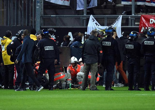 Police, stadium staff and rescuers attend to the wounded Lille LOSC' supporters following collapse of a barrier during their French Ligue 1 match against Amiens, at the Licorne stadium in Amiens, on September 30, 2017 (AFP Photo/FRANCOIS LO PRESTI)