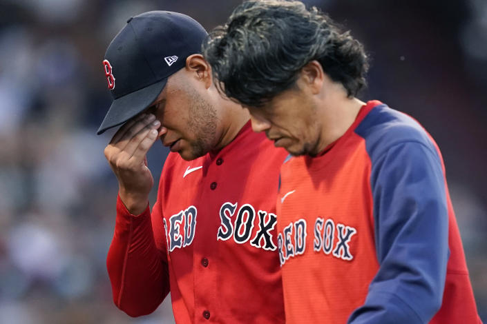 Boston Red Sox starting pitcher Eduardo Rodriguez, left, leaves the baseball game with an injury, accompanied by team trainer Masai Takahashi during the second inning of the team's game against the New York Yankees at Fenway Park, Friday, July 23, 2021, in Boston. (AP Photo/Elise Amendola)