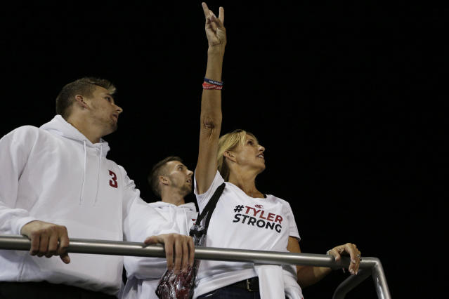 """Kym Hilinski watches the video board with her sons <a class=""""link rapid-noclick-resp"""" href=""""/ncaaf/players/299058/"""" data-ylk=""""slk:Ryan Hilinski"""">Ryan Hilinski</a>, left, and Kelly Hilinski before a game between Washington State and San Jose State. Kym Hilinski's son Tyler Hilinski died by suicide in January 2018. (AP Photo/Young Kwak)"""
