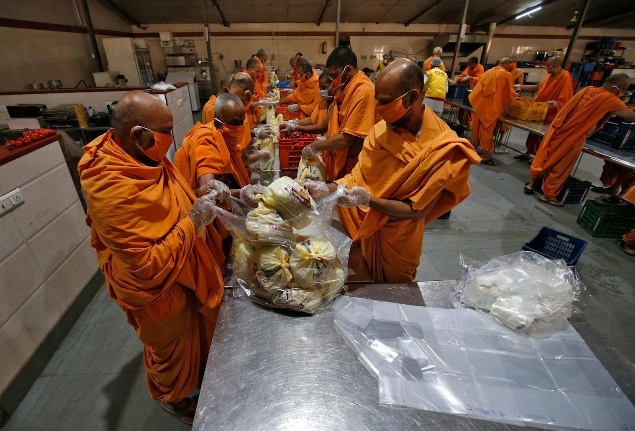 Members of Bochasanwasi Akshar Purushottam Sanstha (BAPS) pack vegetables inside a community kitchen to be distributed amongst poor people during a 21-day nationwide lockdown to limit the spreading of Coronavirus disease (COVID-19), in Ahmedabad, India, March 27, 2020. REUTERS/Amit Dave