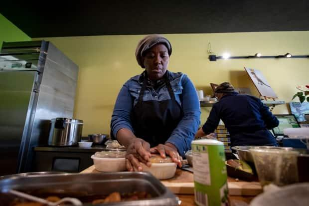 Ikeila Wright readies takeout packages in her Toronto restaurant, One Love Vegetarian. She grew up eating beef, and says food is a personal choice, but hopes people will also make it 'a conscious choice.' (Evan Mitsui - image credit)
