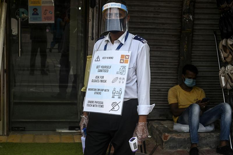 A private security guard wearing a face shield and a placard displaying safety measures to implement against the spread of the COVID-19 coronavirus waits to check the body temperature of customers outside a shop in New Delhi on June 25, 2020. (Photo by Sajjad HUSSAIN / AFP) (Photo by SAJJAD HUSSAIN/AFP via Getty Images)