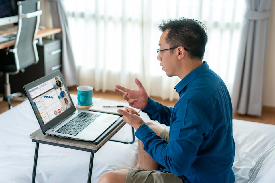 Mixed race businessman wearing business blue shirt on top and short sweatpants on bottom, showing other people on screen in formal fridays business outfits meeting online in bedroom at home.