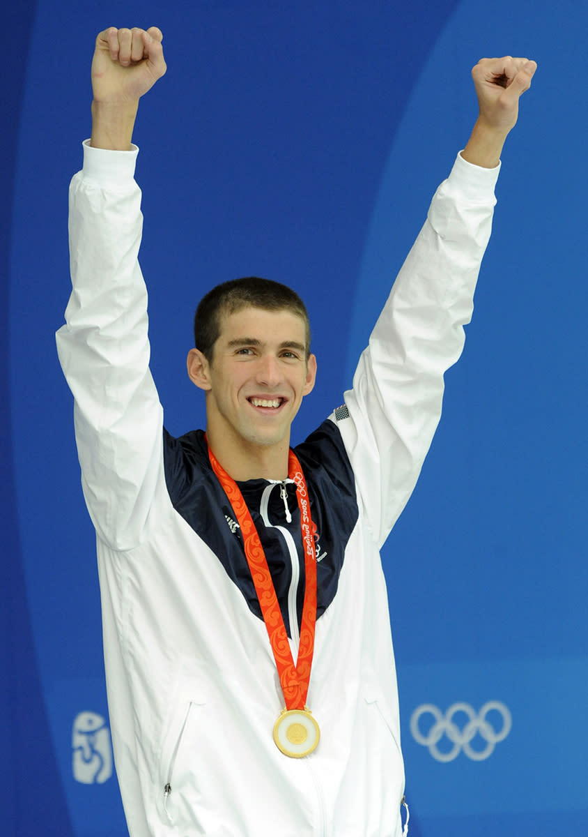<p>Michael Phelps with his gold medal after winning the 100m butterfly final at the Beijing 2008 Olympic Games on August 16, 2008. It was with this prize that Phelps tied Mark Spitz's record of winning seven gold medals in a single Olympic Games. (Bob Thomas/Getty Images)</p>