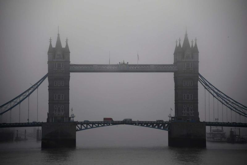 The Tower Bridge emerges from the thick fog in London on Saturday: AP