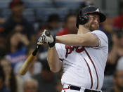 Atlanta Braves' Brian McCann (16) follows through on a three-run home run in the third inning of a baseball game against the Colorado Rockies in Atlanta, Wednesday, July 31, 2013. (AP Photo/John Bazemore)