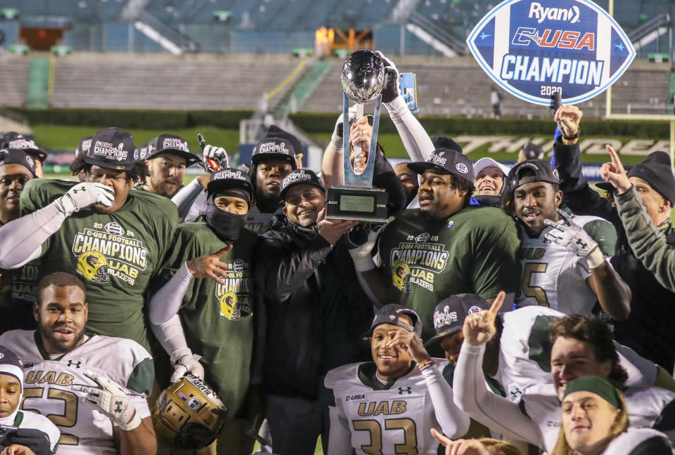 Dec 18, 2020; Huntington, West Virginia, USA; UAB Blazers head coach Bill Clark raises the trophy and celebrates with his players after defeating the Marshall Thundering Herd for the Conference USA Championship at Joan C. Edwards Stadium. Mandatory Credit: Ben Queen-USA TODAY Sports