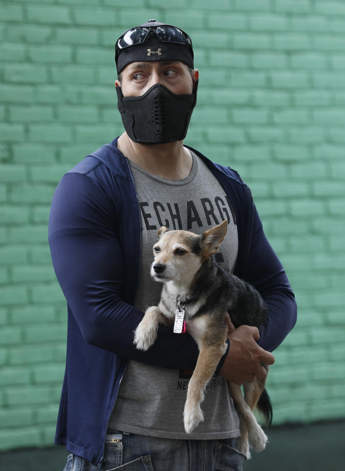 A man holds his dog as he stands outside his home while they wait for the all-clear to return to their apartment, after an earthquake in Mexico City, Tuesday, June 23, 2020. The earthquake struck near the Huatulco resort in southern Mexico on Tuesday morning, swayed buildings in Mexico City and sent thousands fleeing into the streets. (AP Photo/Eduardo Verdugo)