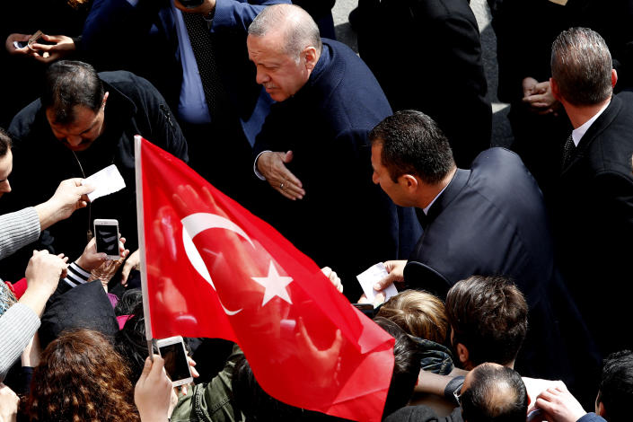 Turkey's President Recep Tayyip Erdogan walks by his supporters at a polling station in Istanbul, Sunday, March 31, 2019. Turkish citizens have begun casting votes in municipal elections for mayors, local assembly representatives and neighbourhood or village administrators that are seen as a barometer of Erdogan's popularity amid a sharp economic downturn.(AP Photo/Lefteris Pitarakis)