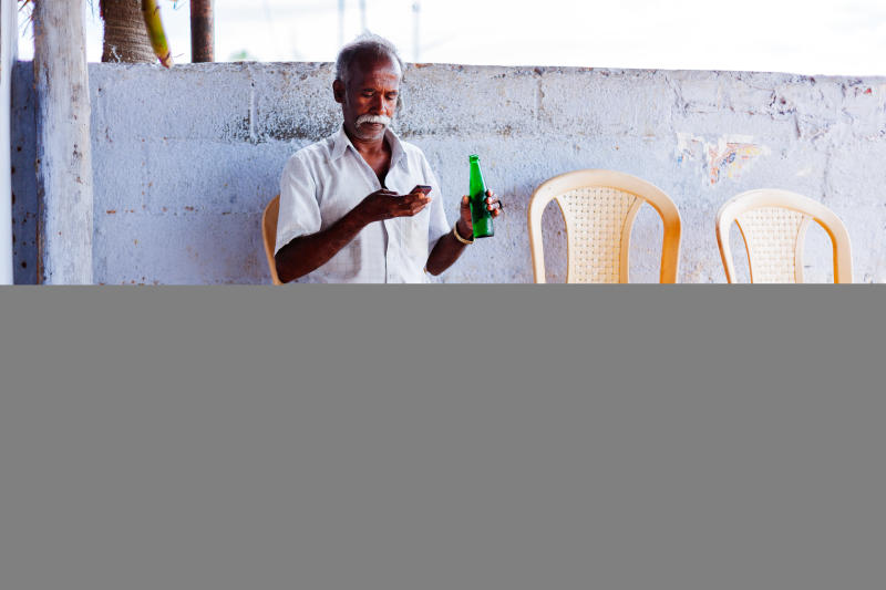 A man chills with a drink and lungi in Tamil Nadu, India. (Himanshu Khagta via Getty Images)