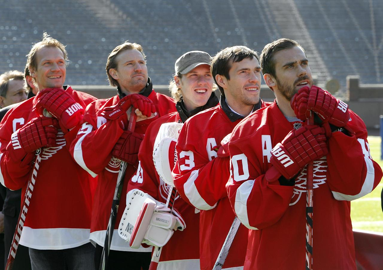 Detroit Red Wings players, from left, Nicklas Lidstrom, of Sweden, Niklas Kronwall, of Sweden, Jimmy Howard, Pavel Datsyuk, of Russia, and Henrik Zetterberg, of Sweden, listen during the announcement of the NHL Winter Classic hockey game at Michigan Stadium in Ann Arbor, Thursday, Feb. 9, 2012. The Toronto Maple Leafs will play the Detroit Red Wings at Michigan Stadium on Jan. 1, 2013. (AP Photo/Paul Sancya)