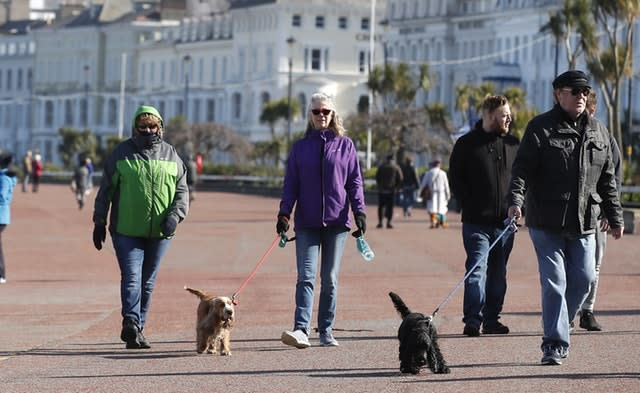 People walk along the promenade in Llandudno, north Wales, as the Government continues to advise the public to reduce social interaction