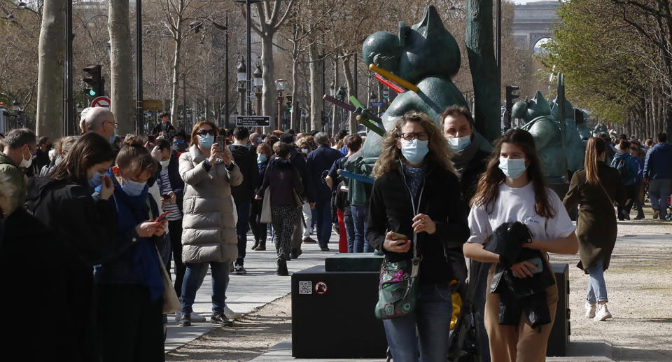 People in France enjoy an outdoor art exhibition in surgical masks. Source: AP